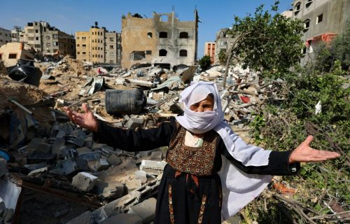 An elderly Palestinian woman reacts in front of her home, damaged by Israeli bombardment, in Beit Lahia in the northern Gaza Strip, on May 20, 2021. - Israel and the Palestinians are mired in their worst conflict in years as Israel pounds the Gaza Strip with air strikes and artillery, while Hamas militants fire rockets into the Jewish state. (Photo by Mohammed ABED / AFP) (Photo by MOHAMMED ABED/AFP via Getty Images)